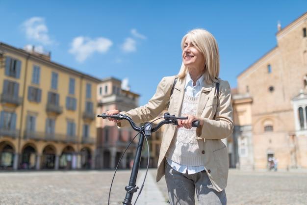 Mujer madura sonriente que sostiene su bicicleta en una plaza grande, día soleado en el país europeo