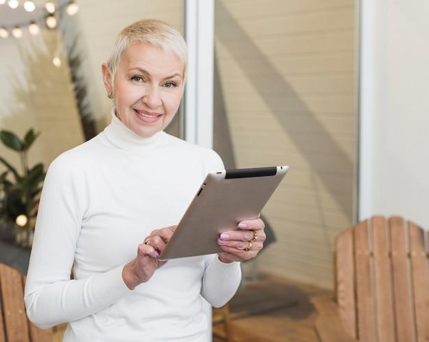 Mujer madura sonriente que usa su tableta