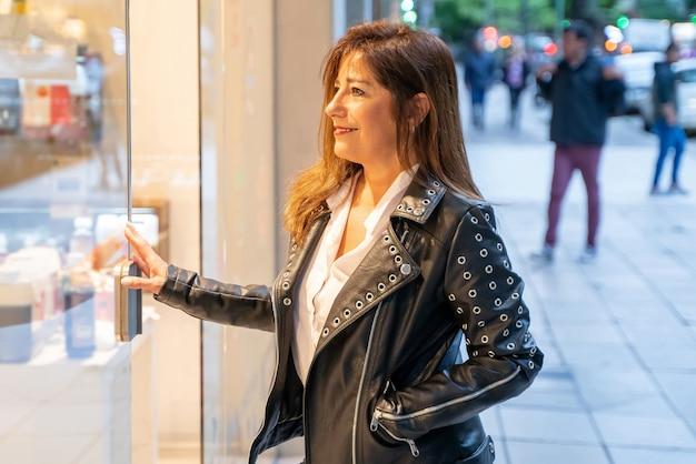 Una mujer madura sonriente revisando el escaparate