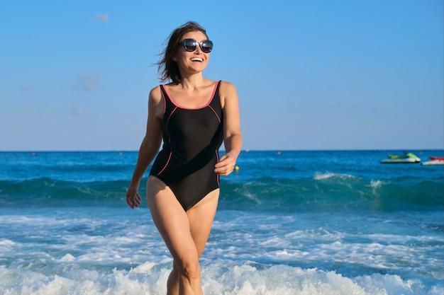 Mujer madura sonriente en traje de baño con gafas de sol caminando por la playa. belleza, salud, cuerpo, relajación para personas de mediana edad. cielo azul, mar con fondo de olas, espacio de copia