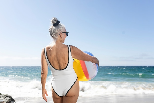 Mujer madura sosteniendo una pelota de playa mientras está en traje de baño