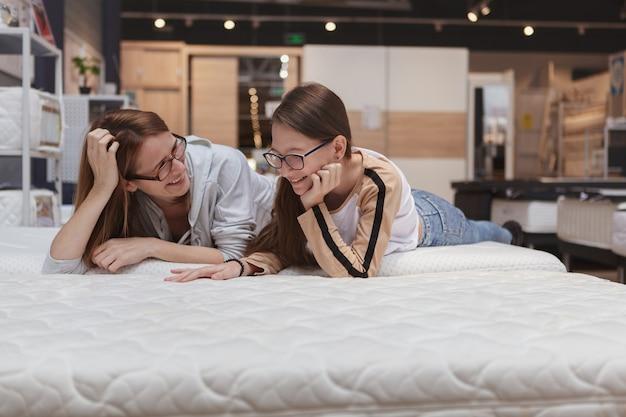 Mujer madura y su hija adolescente tratando de cama ortopédica en la tienda de muebles