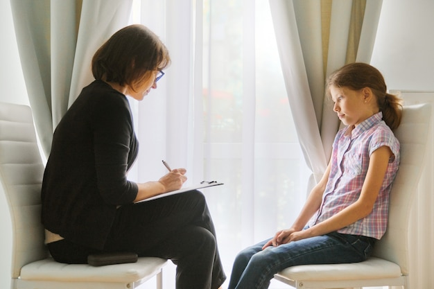 Mujer maestra de escuela primaria prueba hablando con niña