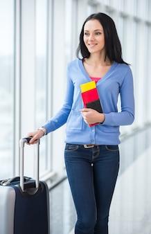 Mujer con maleta y pasaporte está lista para viajar.