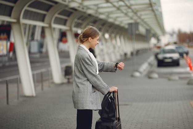 Mujer con maleta de pie en el aeropuerto