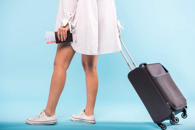 Mujer con maleta rodante y tickets