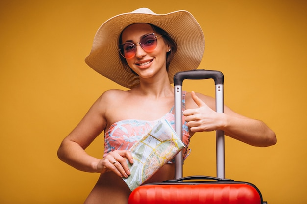 Mujer con maleta roja y mapa de viaje en un traje de baño aislado