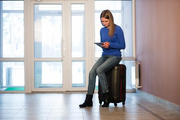 Mujer con maleta y tableta después de viajar en casa