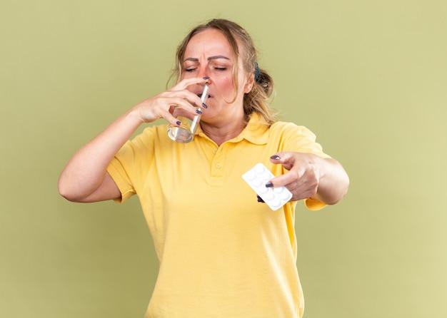 Mujer malsana en camisa amarilla que se siente terrible sosteniendo un vaso de agua y pastillas de agua potable que sufren de gripe y resfriado de pie sobre la pared verde