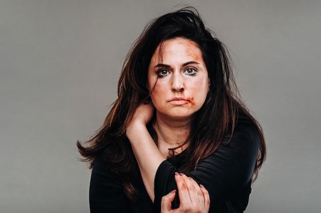 Una mujer maltratada en ropa negra sobre una pared gris aislada