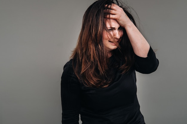 Una mujer maltratada vestida de negro sobre un fondo gris aislado. la violencia contra las mujeres.