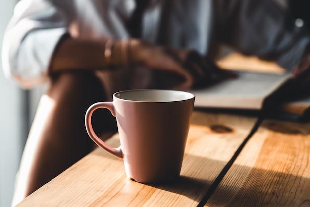 Mujer en la mañana bebe café y lee un libro antiguo con una camisa blanca