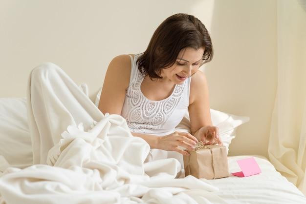 Mujer en la mañana en la cama disfruta de regalo