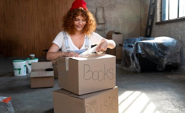 Mujer manejando pertenencias en cajas de cartón para mudarse a casa nueva