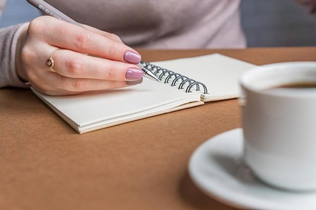 Mujer con manicura escribiendo en el cuaderno. freelancer trabajando en la cafetería.