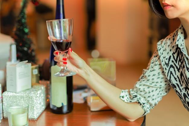 Mujer en manicura roja con vaso de vino tinto.