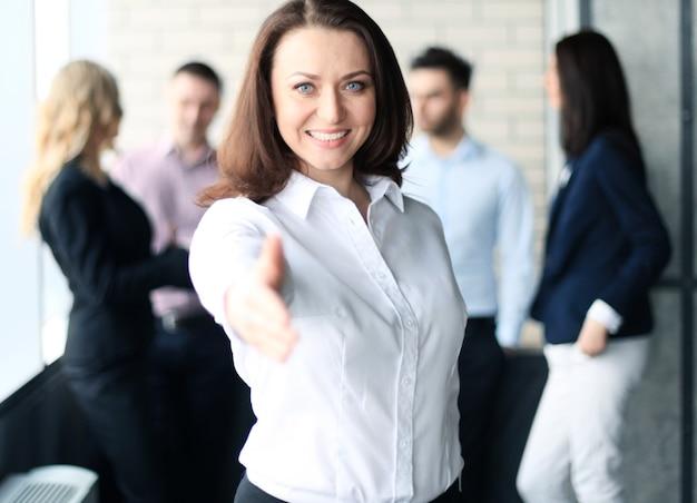 Mujer con la mano abierta lista para el apretón de manos en la oficina.