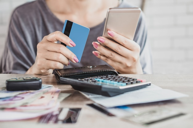 Mujer mano calculando deuda de tarjeta de crédito con teléfono inteligente