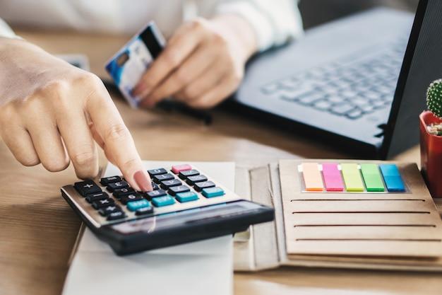 Mujer mano calculando gastos con tarjetas de crédito