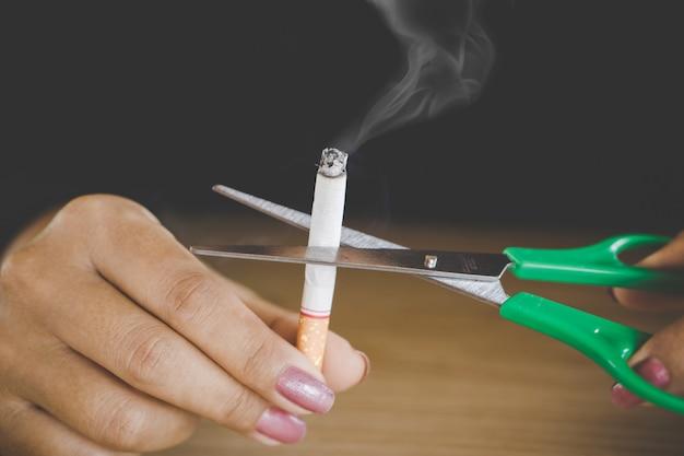 Mujer mano cortar cigarrillo dejar de fumar