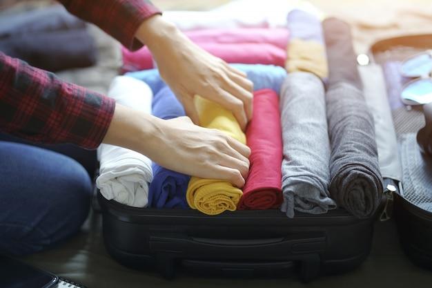 Mujer mano empacar ropa en bolsa de maleta en la cama