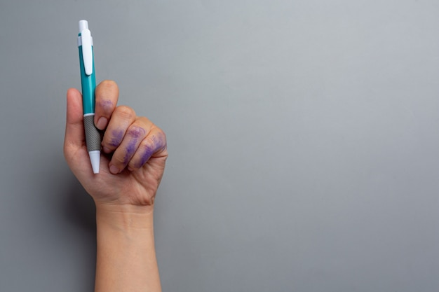 Una mujer con la mano izquierda con un bolígrafo. concepto del día del zurdo.