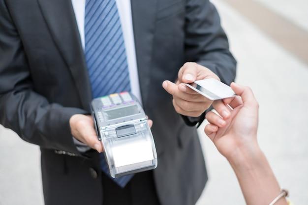 Mujer de mano pagando tarjeta de crédito con terminal de pago con cajero hombre