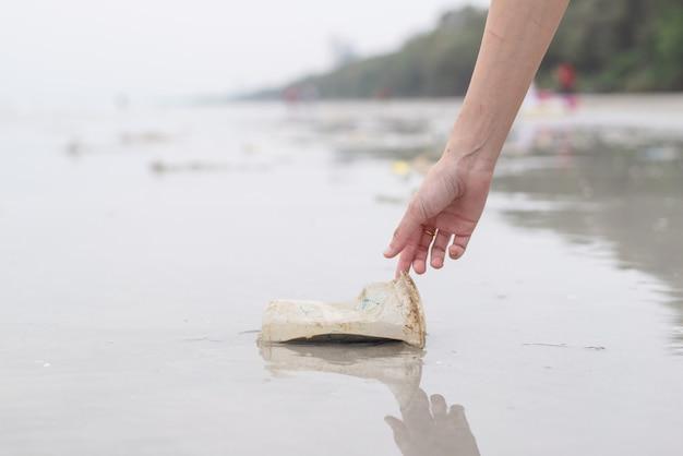 Mujer de mano recogiendo plástico taza de limpieza en la playa