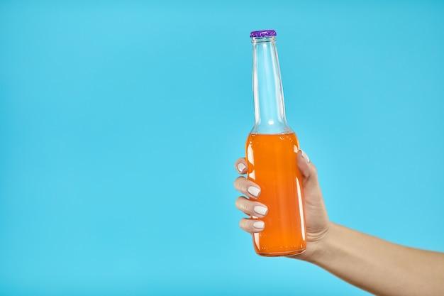 Mujer mano sosteniendo una botella de bebida alcohólica