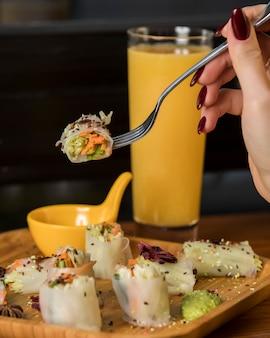 Mujer mano sostiene en tenedor rollitos de primavera con pepino, zanahoria y lechuga