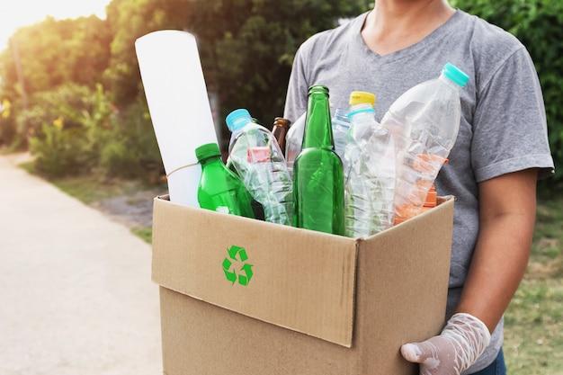Mujer mano sujetando la caja de basura para reciclar