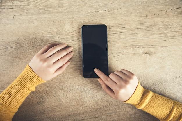 Mujer mano teléfono inteligente sobre la mesa