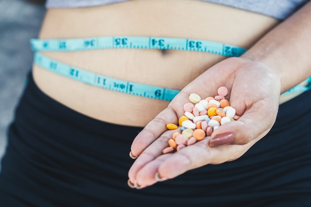Mujer mano tomando sobredosis píldoras de dieta