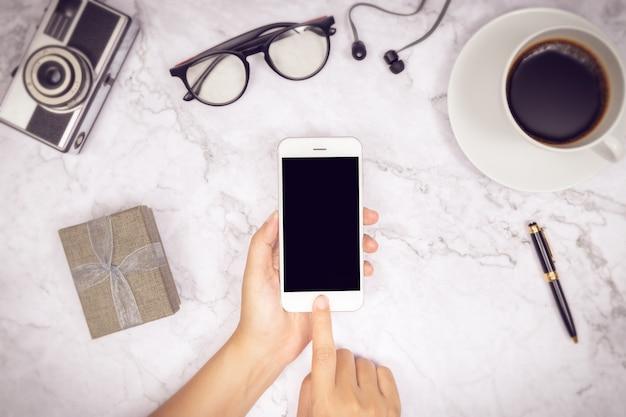 Mujer mano uso maqueta de teléfono móvil en blanco pantalla negra con dedo en pantalla táctil