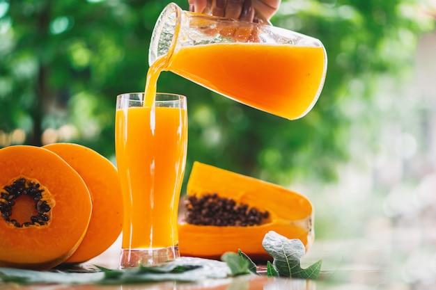 Mujer mano vertiendo jugo de papaya en vasos