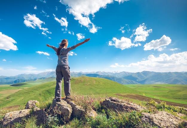 Mujer con manos levantadas en colinas