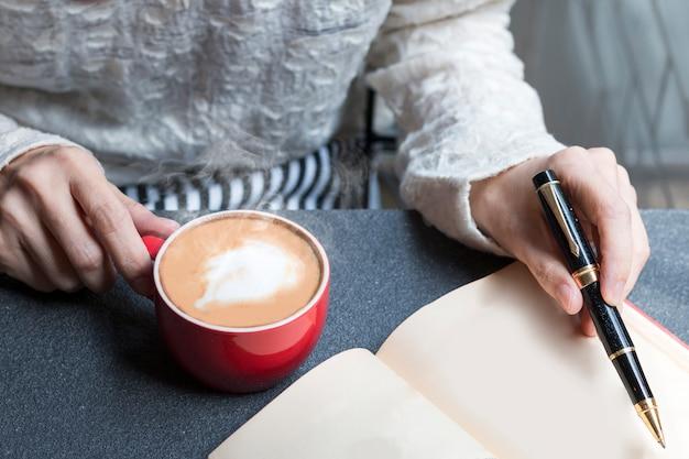 Mujer de las manos que sostienen la taza caliente de café con leche y que escriben en el libro.