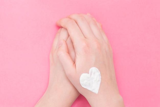 Mujer de manos en rosa. crema hidratante para pieles limpias y suaves en invierno.
