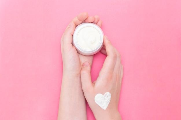 Mujer de manos con un tarro de crema en rosa