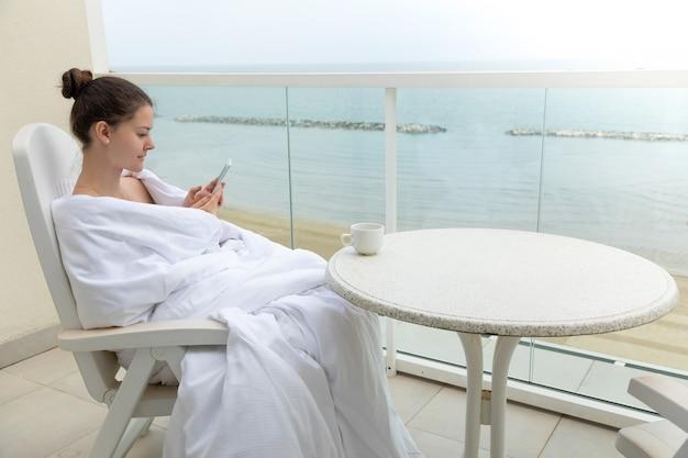 Mujer en manta blanca con teléfono inteligente en la terraza de su casa