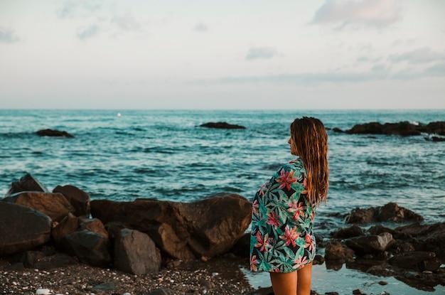 Mujer en manta de pie en la orilla del mar