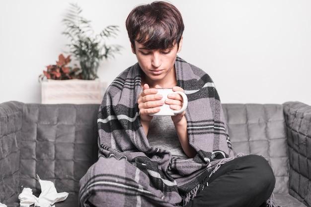 Mujer con la manta que se sienta en el sofá que mira la taza de café