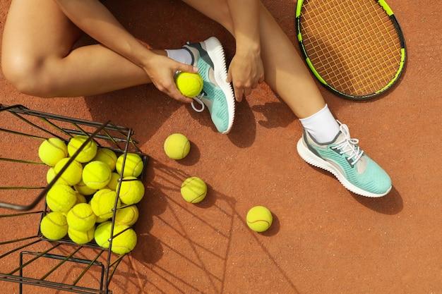 Mujer mantenga pelota de tenis en cancha de arcilla con raqueta y pelotas