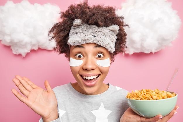 La mujer mantiene la palma levantada oye algo inesperado sonríe ampliamente sostiene un tazón de cereales con una cuchara vestida con un traje de dormir con los ojos vendados