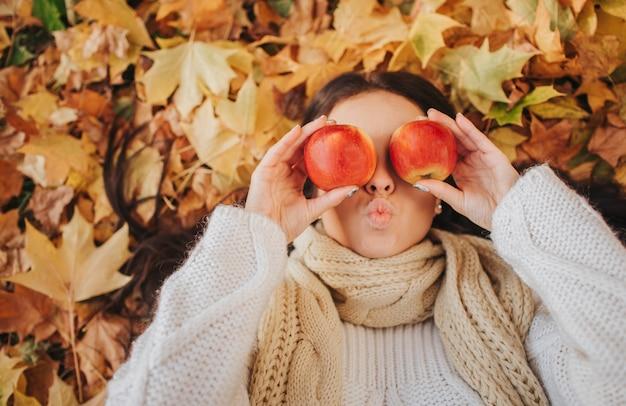 Mujer con manzana roja en el parque otoño. concepto de la estación, de la fruta y de la gente - muchacha hermosa que miente en las hojas de tierra y de otoño. modelo femenino se divierte en el otoño.