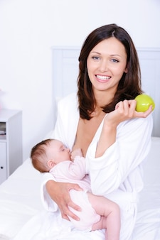 Mujer con manzana verde amamantando a su bebé
