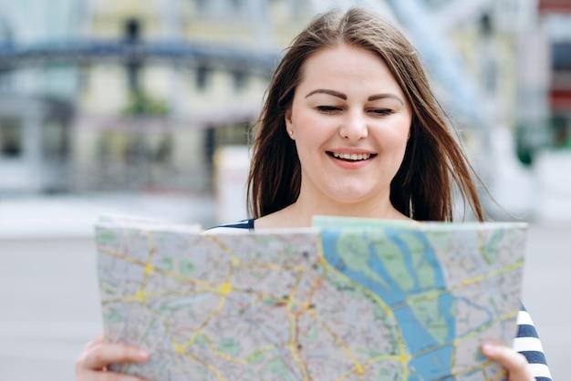 Mujer con un mapa en sus manos camina por las calles de la ciudad, buscando el camino correcto