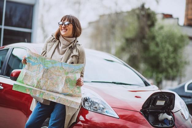 Mujer con mapa de viaje viajando en auto electro.