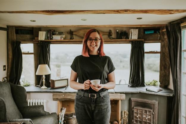 Mujer con una maqueta de taza de café en una cabaña