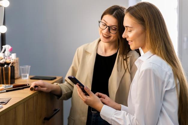 Mujer y maquilladora mirando el teléfono